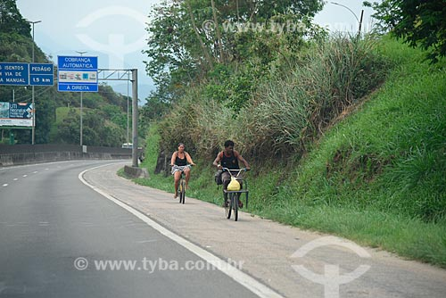 Pessoas andando de bicicleta no acostamento da Rodovia Washington Luís (BR-040)   - Duque de Caxias - Rio de Janeiro (RJ) - Brasil