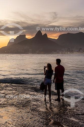 Casal observando o pôr do sol a partir da Pedra do Arpoador  - Rio de Janeiro - Rio de Janeiro (RJ) - Brasil