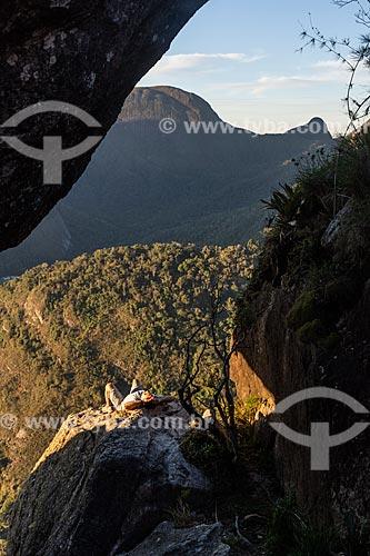 Homem deitado em rocha durante o pôr do sol - Vista do Pico Caixa de Fósforo no Parque Estadual dos Três Picos  - Teresópolis - Rio de Janeiro (RJ) - Brasil