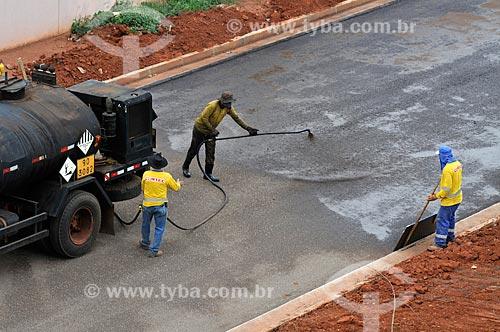 Trabalhador esparramando piche em rua que está sendo pavimentada  - São José do Rio Preto - São Paulo (SP) - Brasil