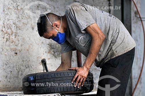 Homem trabalhando em borracharia e usando máscara por causa da Crise do Coronavírus  - Mirassol - São Paulo (SP) - Brasil