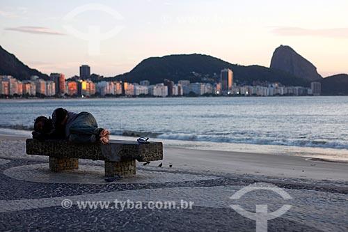 Morador de rua dormindo em banco na orla da Praia de Copacabana durante a quarentena - Crise do Coronavírus  - Rio de Janeiro - Rio de Janeiro (RJ) - Brasil