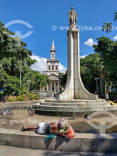 Morador de rua dormindo no chafariz do Largo do Machado com a Igreja Matriz de Nossa Senhora da Glória (1872) ao fundo  - Rio de Janeiro - Rio de Janeiro (RJ) - Brasil