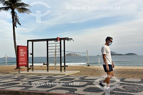 Pessoa caminhando sozinha no calçadão da orla da Praia de Ipanema usando máscara de proteção - Crise do Coronavírus  - Rio de Janeiro - Rio de Janeiro (RJ) - Brasil