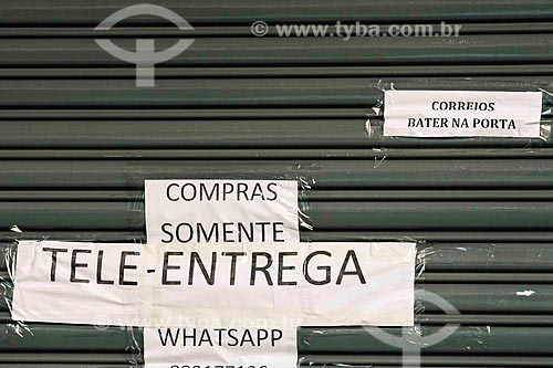 Cartaz na porta de loja informando  que só está funcionando por tele-entrega - Crise do Coronavírus  - Porto Alegre - Rio Grande do Sul (RS) - Brasil