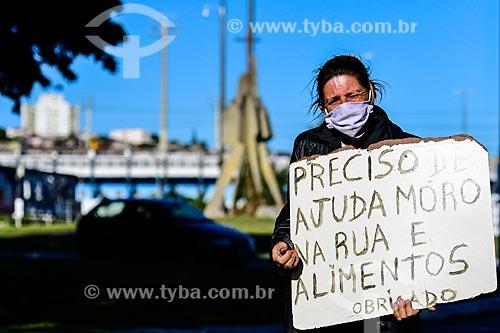 Moradora de rua usando máscara de proteção  segura cartaz pedindo ajuda - Crise do Coronavírus  - Porto Alegre - Rio Grande do Sul (RS) - Brasil