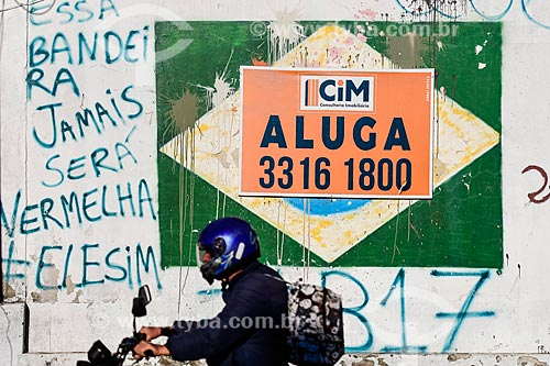 Motoqueiro passa em frente a placa sugerindo que o Brasil está para alugar - Crise do Coronavírus  - Porto Alegre - Rio Grande do Sul (RS) - Brasil