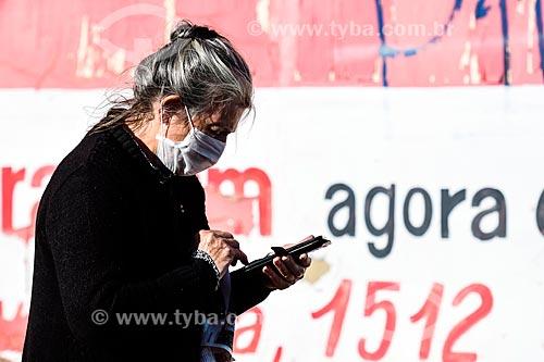Mulher usando máscara de proteção na rua enquanto utiliza telefone celular - Crise do Coronavírus  - Porto Alegre - Rio Grande do Sul (RS) - Brasil