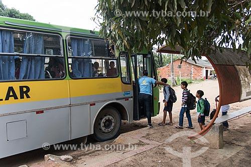Crianças indígenas entrando em ônibus escolar - Terra Indígena Pau Brasil da etnia Tupiniquim - ACRÉSCIMO DE 100% SOBRE O VALOR DE TABELA  - Aracruz - Espírito Santo (ES) - Brasil
