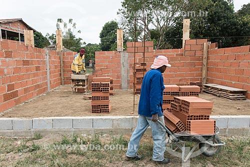 Indígena assentando tijolos em construção - Terra Indígena Pau Brasil da etnia Tupiniquim - ACRÉSCIMO DE 100% SOBRE O VALOR DE TABELA  - Aracruz - Espírito Santo (ES) - Brasil