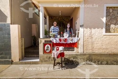Altar em homenagem ao Divino Espírito Santo, (Padroeiro da cidade) montado na calçada de uma casa  - Ao fundo Mulher utilizando máscara de proteção contra o Covid 19 - Crise do Coronavírus - Guarani - Minas Gerais (MG) - Brasil