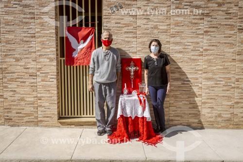 Altar em homenagem ao Divino Espírito Santo, (Padroeiro da cidade) montado na calçada de uma casa - Casal utilizando máscara de proteção contra o Covid 19 - Crise do Coronavírus - Guarani - Minas Gerais (MG) - Brasil