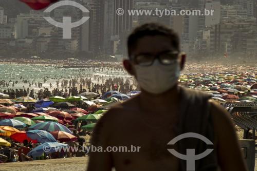 Pessoa usando máscara de proteção e a Praia de Ipanema lotada ao fundo - Crise do Coronavírus - Rio de Janeiro - Rio de Janeiro (RJ) - Brasil
