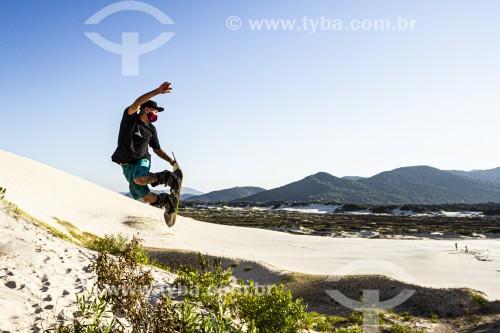 Praticante de sandboard usando máscara de proteção contra a Covid 19 nas dunas da Praia Joaquina - Crise do Coronavírus - Florianópolis - Santa Catarina (SC) - Brasil