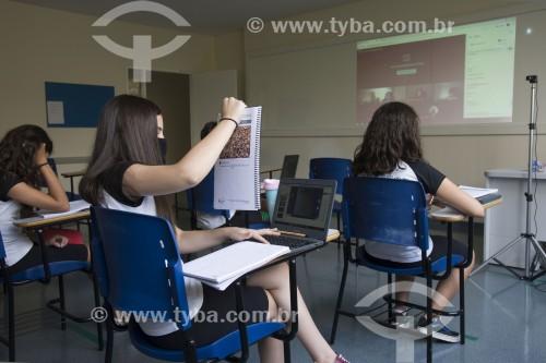Sala de aula de colégio particular com parte dos alunos em aula presencial e outra parte em aula remota em função da crise do Coronavírus - Aluna fotografando livro com câmera do notebook - Sorocaba - São Paulo (SP) - Brasil