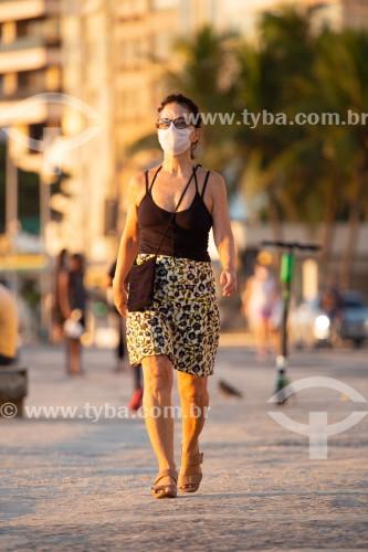 Mulher com máscara protetora contra a Covid-19 caminhando no calçadão da Praia de Copacabana - Rio de Janeiro - Rio de Janeiro (RJ) - Brasil