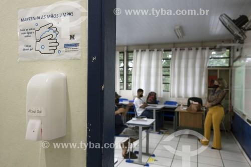 Dispenser com álcool gel na entrada da sala de aula e sala de aula com distanciamento entre cadeiras e alunos usando máscaras de proteção por causa da Covid 19 - São Paulo - São Paulo (SP) - Brasil