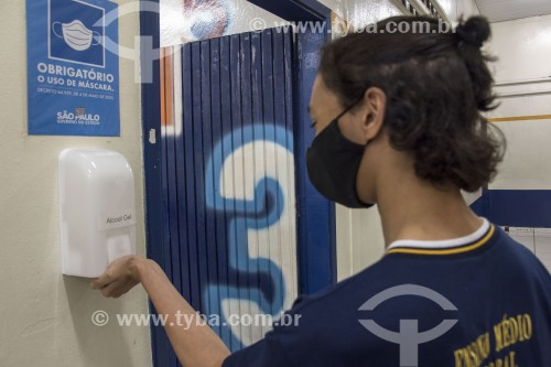 Aluno usando máscara e higienizando as mãos com álcool gel na entrada da sala de aula de escola estadual de ensino médio - São Paulo - São Paulo (SP) - Brasil