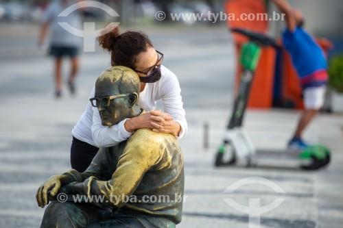 Mulher abraçada à estátua do poeta Carlos Drummond de Andrade na Praia de Copacabana - Rio de Janeiro - Rio de Janeiro (RJ) - Brasil