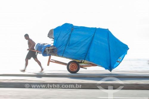 Homem puxando carrinho de burro-sem-rabo com cadeiras de praia na orla da Praia de Copacabana - Rio de Janeiro - Rio de Janeiro (RJ) - Brasil