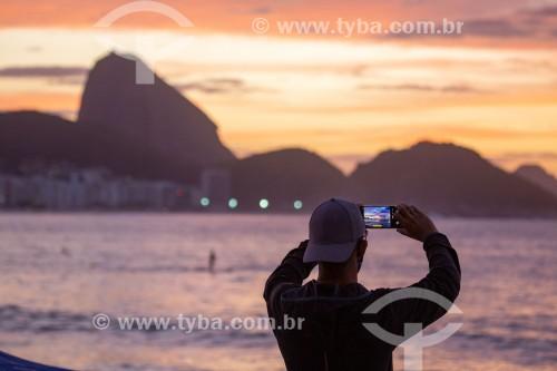 Homem fotografando com telefone celular o nascer do sol na praia de Copacabana com o Pão de Açúcar ao fundo - Rio de Janeiro - Rio de Janeiro (RJ) - Brasil