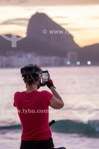 Mulher fotografando com telefone celular o nascer do sol na praia de Copacabana com o Pão de Açúcar ao fundo - Rio de Janeiro - Rio de Janeiro (RJ) - Brasil