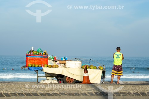 Vendedor ambulante com carrinho de burro-sem-rabo vendendo bebidas e água de coco na orla da Praia do Arpoador - Rio de Janeiro - Rio de Janeiro (RJ) - Brasil