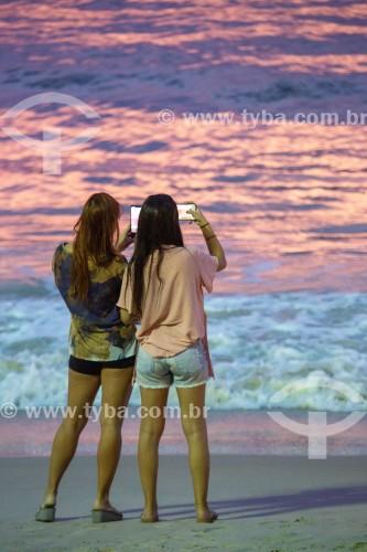 Mulheres fotografando com telefone celular o nascer do sol na Praia de Copacabana - Rio de Janeiro - Rio de Janeiro (RJ) - Brasil