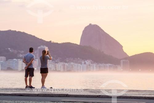 Casal fotografando com telefone celular o nascer do sol na Praia de Copacabana com o Pão de Açúcar ao fundo - Rio de Janeiro - Rio de Janeiro (RJ) - Brasil