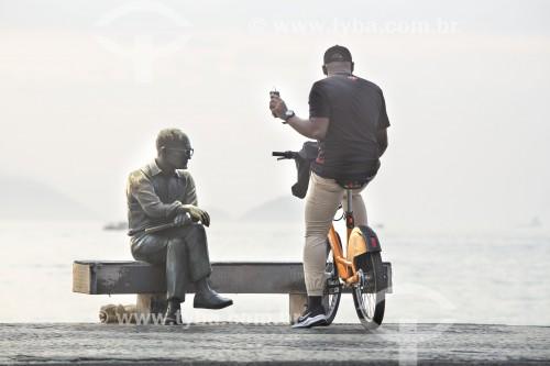 Ciclista com telefone celular no calçadão da Praia de Copacabana próximo à estátua do poeta Carlos Drummond de Andrade - Rio de Janeiro - Rio de Janeiro (RJ) - Brasil