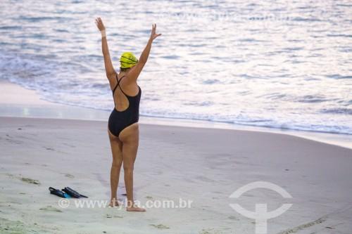 Mulher praticante de natação em mar aberto fazendo aquecimento antes de entrar na água - Posto 6 - Rio de Janeiro - Rio de Janeiro (RJ) - Brasil