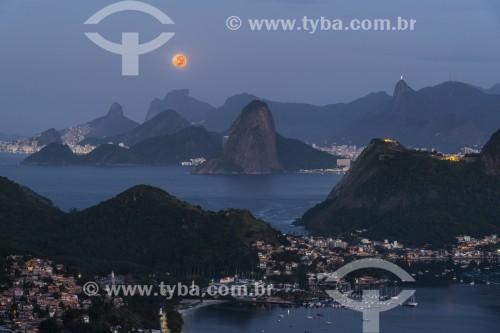Vista do Rio de Janeiro a partir do Parque da Cidade de Niterói ao amanhecer com a lua cheia sobre as montanhas - Niterói - Rio de Janeiro (RJ) - Brasil
