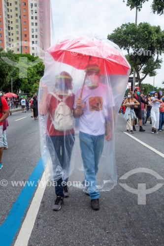 Casal com guarda-chuva e capa de plástico para proteção contra a Covid 19  - Manifestação de 19 de junho contra o governo do Presidente Jair Messias Bolsonaro - Rio de Janeiro - Rio de Janeiro (RJ) - Brasil