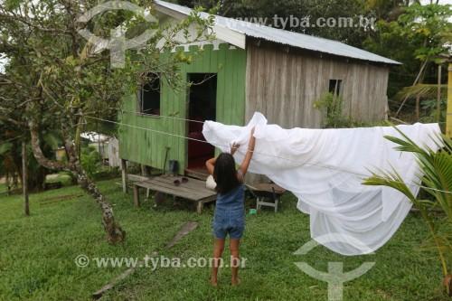 Mulher pendurando roupas em varal - moradia típica na Reserva de Desenvolvimento Sustentável Mamirauá - Uarini - Amazonas (AM) - Brasil
