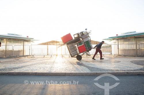 Homem puxando carrinho de burro-sem-rabo com cadeiras de praia na orla da Praia de Ipanema  - Rio de Janeiro - Rio de Janeiro (RJ) - Brasil