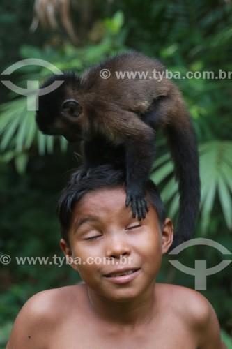 Criança com um Macaco Prego - Reserva de Desenvolvimento Sustentável Mamirauá - Uarini - Amazonas (AM) - Brasil