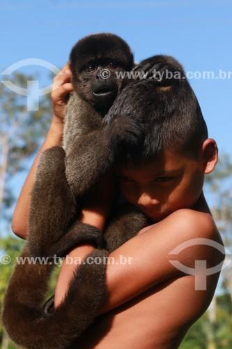 Criança com um Macaco Barrigudo (Lagothrix lagotricha) - Reserva de Desenvolvimento Sustentável Mamirauá - Uarini - Amazonas (AM) - Brasil
