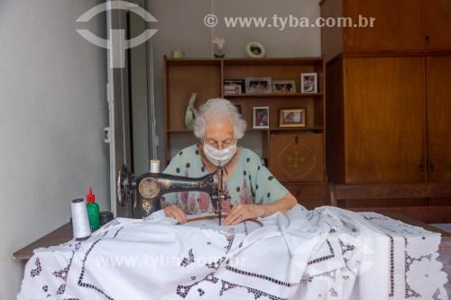 Costureira idosa usando máscara de proteção contra a Covid-19 enquanto trabalha - Guarani - Minas Gerais (MG) - Brasil