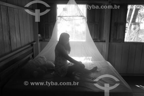 Mulher ribeirinha de origem indígena em moradia típica - Cama com mosquiteiro - Manaus - Amazonas (AM) - Brasil