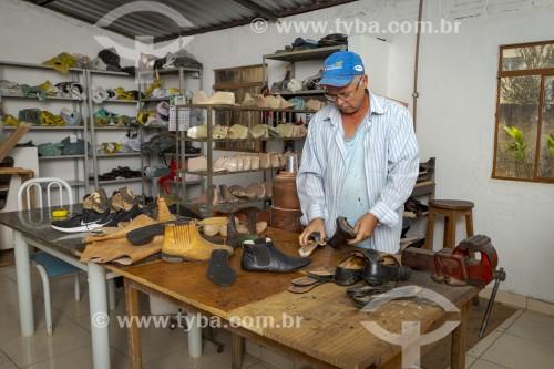 Sapateiro durante conserto manual de calçados - Guarani - Minas Gerais (MG) - Brasil