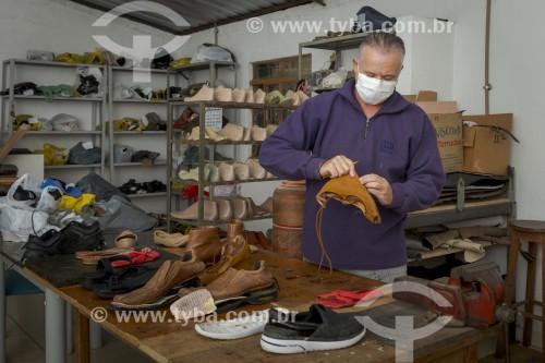 Sapateiro durante conserto manual de calçados utilizando máscara de proteção contra a Covid-19 - Guarani - Minas Gerais (MG) - Brasil
