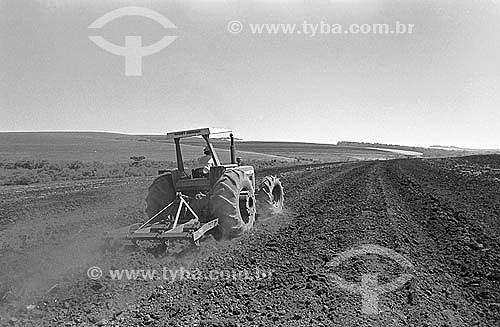 Agricultura - Máquina agrícola - Trator trabalhando a terra para plantio