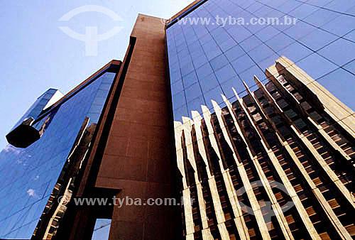 Arquitetura moderna - Edifício com fachada de vidro refletindo o céu e outro prédio