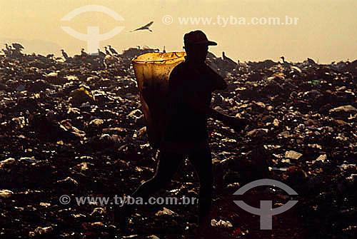 Silhueta de catadores de lixo com balde no Aterro Sanitário - Jardim Gramacho - RJ - Brasil / Data: 2010