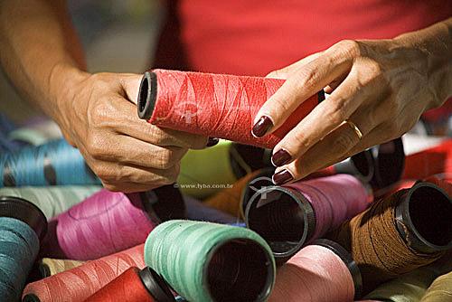 Mãos segurando carretéis de linha  - Brasil