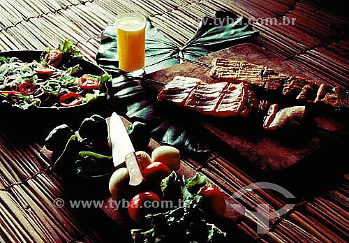 Culinária - costeleta de porco, copo com suco de laranja, tomates, cebolas e salada verde.