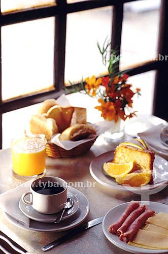 Café da manhã - xícara de café, bolo, presunto, queijo, suco de laranja e cesta com pães.