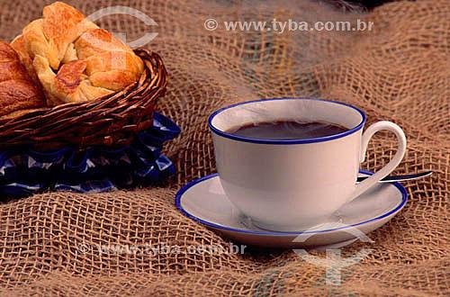 Xícara de café e cesta com croissant