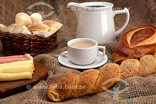 Mesa de café da manhã: cesta com pães, queijo, xícara de café com leite e bule de café.
