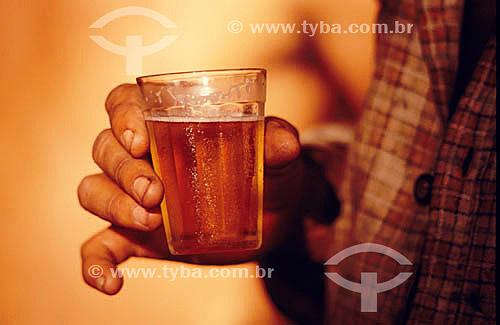 Detalhe da mão de um homem segurando um copo com cerveja